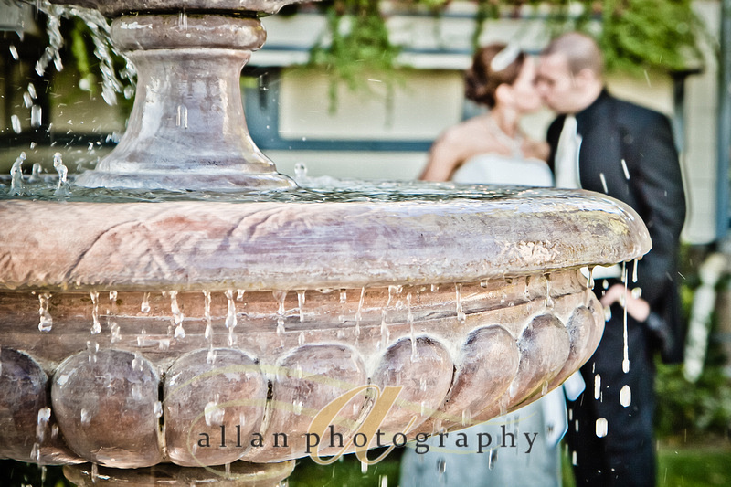 Bride and groom kiss by the fountain at Barone's in pleasanton